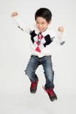 Den asiatiska gulliga pojken hoppar med leendeframsidan Arkivfoto
