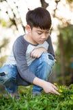 Den asiatiska gulliga pojken upptäcker glädjen av den gula blomman arkivfoto