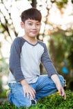 Den asiatiska gulliga pojken upptäcker glädjen av den gula blomman royaltyfria foton