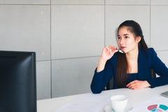 Den asiatiska härliga affärskvinnan har bekymmer i henne som tänker fotografering för bildbyråer