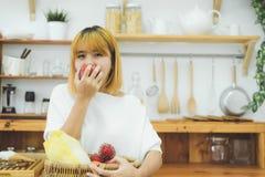 Den asiatiska härliga kvinnan äter det röda äpplet i köket på henne hem Den lyckliga nätta asiatiska kvinnlign äter friskhetfrukt Arkivbilder