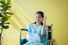 Den asiatiska h?rliga kvinnliga patienten lyfter upp ditt reko teckensymbol f?r h?nder och att sitta p? rullstolen p? sjukhuset,  arkivfoto