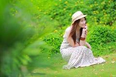 Den asiatiska härliga unga flickan, bär den blom- maxi klänningen Fotografering för Bildbyråer
