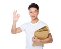 Den asiatiska hållen för den unga mannen med mappen och det ok tecknet gör en gest Fotografering för Bildbyråer