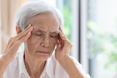 Den asiatiska höga kvinnan har huvudvärken som trycker på hennes huvud med hennes händer, meddelar tecknen av svindel; svindel; m arkivbild