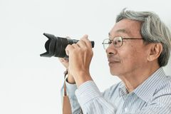 Den asiatiska hobbyen för gamal manexponeringsglasavgången som fotograf tar ett fotografi royaltyfri bild