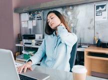 Den asiatiska idérika märkes- kvinnan fångar hennes hals för att smärta från hårt arbete royaltyfri foto