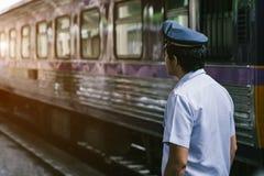 Den asiatiska järnväg polisen som utanför ser på järnvägspår royaltyfri foto