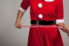 Den asiatiska julflickan i Santa Claus kläder bantar med att mäta royaltyfri fotografi