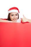 Den asiatiska julflickan med Santa Claus beklär upp tummar med bla Arkivbild