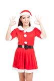 Den asiatiska julflickan med Santa Claus kläder visar det reko tecknet Arkivfoto