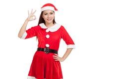 Den asiatiska julflickan med Santa Claus kläder visar det reko tecknet Royaltyfria Bilder