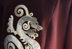 Den asiatiska kinesiska draken som gjordes av fiskhud, tillverkade på vinous tyg Royaltyfri Bild