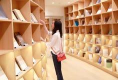 Den asiatiska kinesiska härliga nätta gulliga kvinnaflickastudenten Teenager läste boken i bokhandelarkivleende royaltyfria bilder