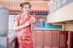 Den asiatiska kinesiska kvinnan i för hållgåva för traditionell kines påse royaltyfri fotografi