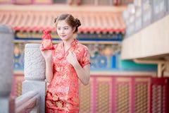 Den asiatiska kinesiska kvinnan i för hållgåva för traditionell kines påse royaltyfria bilder