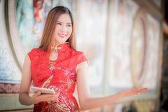 Den asiatiska kinesiska kvinnan i tablel c för traditionell kines och håll royaltyfria bilder