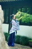 Den asiatiska kinesiska kvinnan i traditionella blått och vit Hanfu klär, spelar i berömda trädgårds- near fönster Arkivfoto