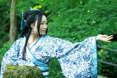 Den asiatiska kinesiska kvinnan i traditionella blått och vit Hanfu klär, spelar i en berömd trädgård Arkivbilder