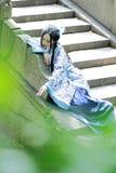 Den asiatiska kinesiska kvinnan i traditionella blått och vit Hanfu klär, spelar i en berömd trädgård Fotografering för Bildbyråer