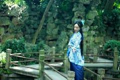 Den asiatiska kinesiska kvinnan i traditionella blått och vit Hanfu klär, spelar i en berömd trädgård på den krokiga bron Royaltyfria Foton