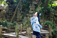 Den asiatiska kinesiska kvinnan i traditionella blått och vit Hanfu klär, spelar i en berömd trädgård på den krokiga bron Arkivfoton