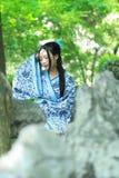 Den asiatiska kinesiska kvinnan i traditionella blått och vit Hanfu klär, spelar i en berömd trädgård, sitter på en forntida sten Royaltyfri Foto