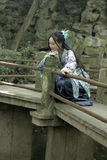Den asiatiska kinesiska kvinnan i traditionella blått och vit Hanfu klär, spelar i en berömd trädgårds- klättring på böjelsebron Royaltyfria Foton