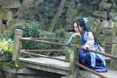 Den asiatiska kinesiska kvinnan i traditionella blått och vit Hanfu klär, spelar i en berömd trädgårds- klättring på böjelsebron Royaltyfria Bilder