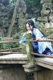 Den asiatiska kinesiska kvinnan i traditionella blått och vit Hanfu klär, spelar i en berömd trädgårds- klättring på böjelsebron Royaltyfri Foto