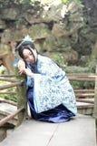 Den asiatiska kinesiska kvinnan i traditionella blått och vit Hanfu klär, spelar i en berömd trädgårds- klättring på böjelsebron Arkivfoto