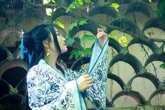 Den asiatiska kinesiska kvinnan i traditionella blått och vit Hanfu klär, spelar i en berömd trädgårds- near vägg Royaltyfri Bild