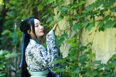 Den asiatiska kinesiska kvinnan i traditionella blått och vit Hanfu klär, spelar i en berömd trädgårds- near vägg Arkivfoto