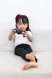 Den asiatiska kinesiska lilla flickan som spelar TV, spelar på soffan Arkivbild