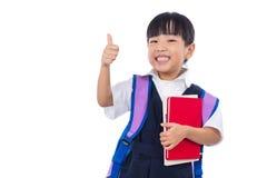 Den asiatiska kinesiska lilla grundskola för barn mellan 5 och 11 årflickavisningen tummar upp Arkivfoto