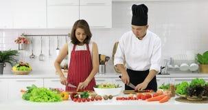 Den asiatiska kocken visar hur man klipper tomater arkivfilmer