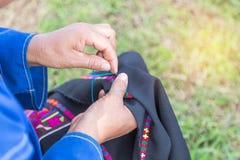 Den asiatiska kullestamkvinnan som broderar den traditionella modellen, handcraft lokal kläder med visaren Royaltyfri Bild