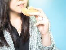 Den asiatiska kvinna30-tal till 40-talhanden med torkdukehållen och äter munken på M Arkivfoton