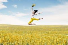 Den asiatiska kvinnaballerina rymmer buketten av blommor som gör ett stort hopp på äng Arkivfoto