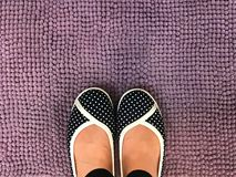 Den asiatiska kvinnafoten bär den tillfälliga skon för pricken på violett matta Royaltyfria Bilder