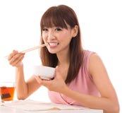 Den asiatiska kvinnan äter ris Arkivbilder