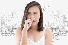 Den asiatiska kvinnan fångar hennes näsa på grund av en dålig lukt royaltyfri fotografi