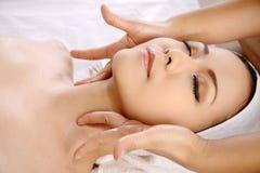 Den asiatiska kvinnan får ansikts- massage arkivfoton