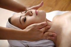 Den asiatiska kvinnan får ansikts- massage royaltyfri fotografi