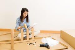 Den asiatiska kvinnan följer anvisning för monterande stol arkivbild
