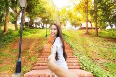 Den asiatiska kvinnan följer mig det lyckliga leendet för den hållande manhanden Arkivbild