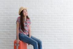 Den asiatiska kvinnan förbereder sig att resa på den vita tegelstenväggen, Lifest royaltyfria foton