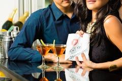 Den asiatiska kvinnan förför mannen i restaurang Royaltyfria Foton