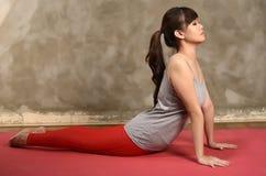 Den asiatiska kvinnan gör yoga Arkivfoto