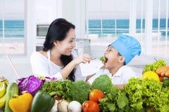 Den asiatiska kvinnan ger hennes son sund mat Arkivbild